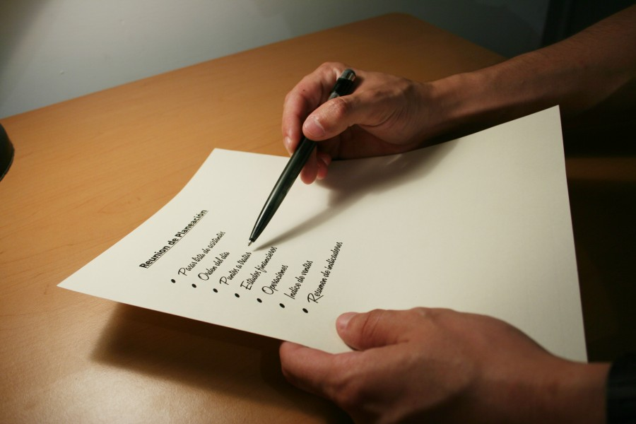 Two hands writing checklist on desk