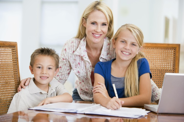 Mother helping her children with homework