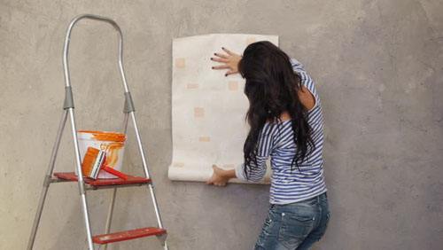 Young woman holding up wallpaper to wall