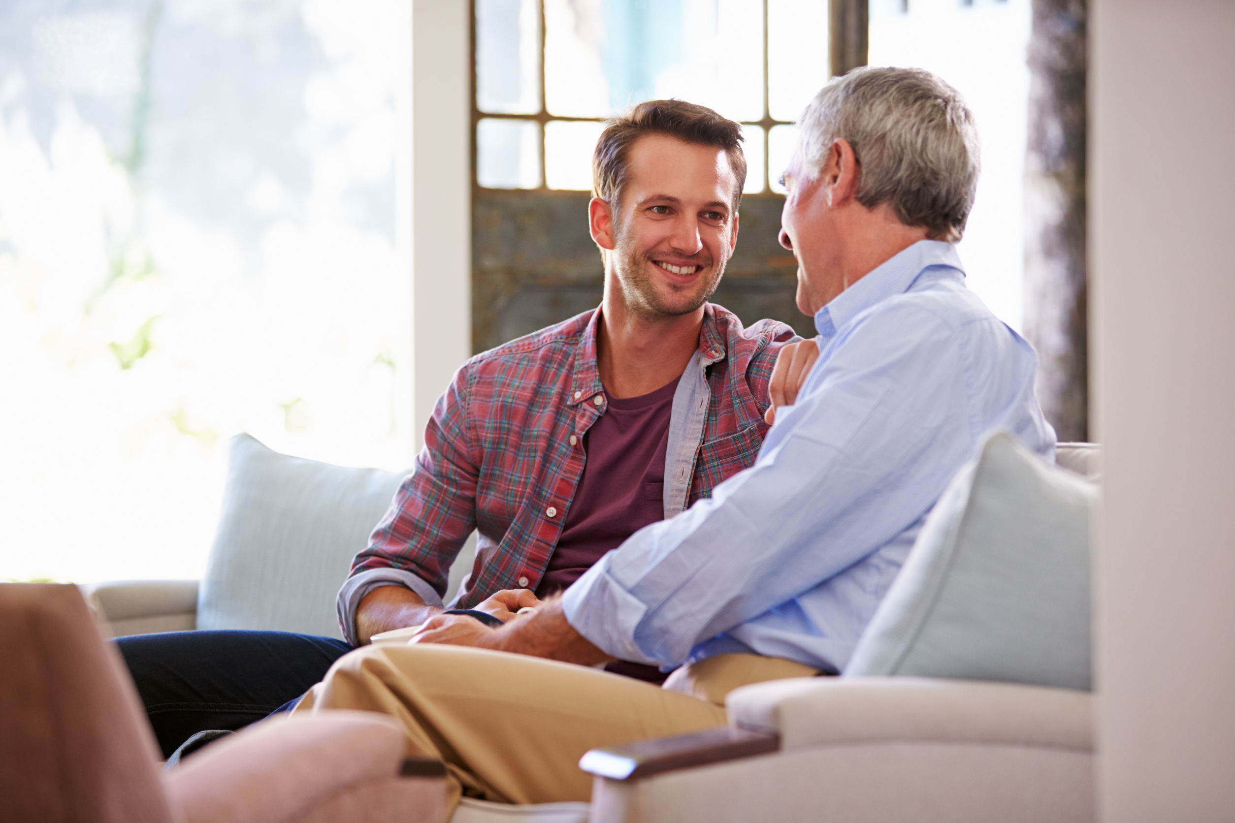 Adult father and son talking on couch