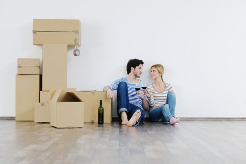 Young couple sitting beside moving boxes